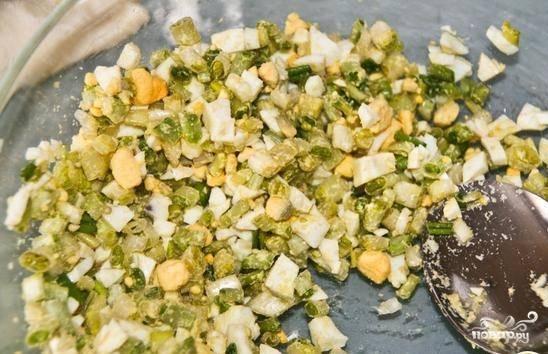 Заранее разморозьте тесто. Сварите вкрутую яйца. Помойте и измельчите черемшу. Соедините её с нарезанными яйцами. Посолите, перемешайте.