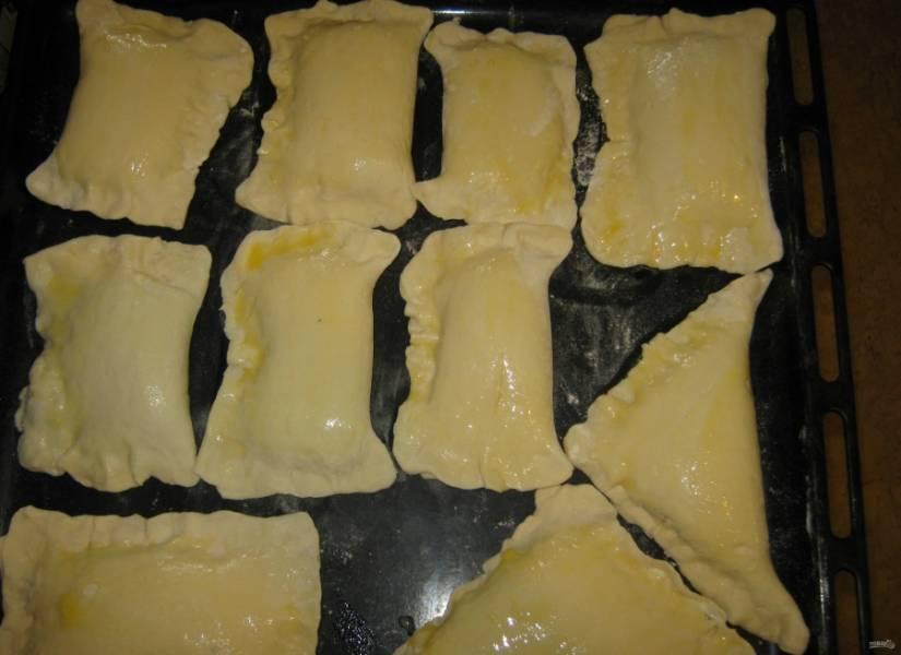 9.Противень посыпаю мукой и выкладываю на него пирожки, смазываю их яйцом для румяной корочки.