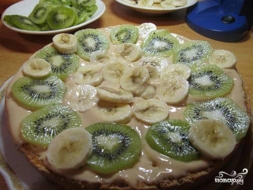 Первый корж выкладываем на большую тарелку, промазываем кремом и выкладываем бананы и киви. Накрываем вторым бисквитом и снова кладем крем и фрукты.