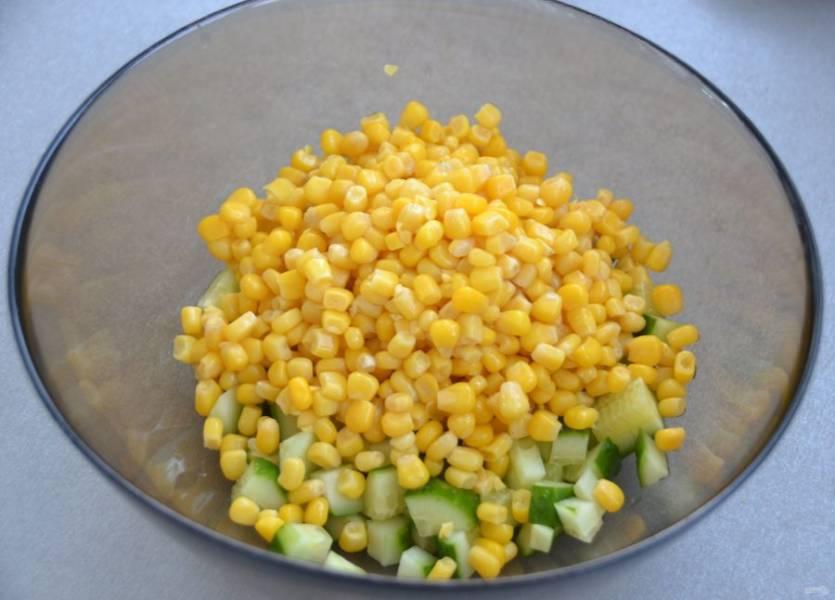 Слейте жидкость с кукурузы и добавьте её к нарезанному огурцу.
