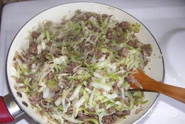 Затем в сковороду добавьте капусту. Перемешайте начинку, тушите её до полуготовности, добавив соль и перец.