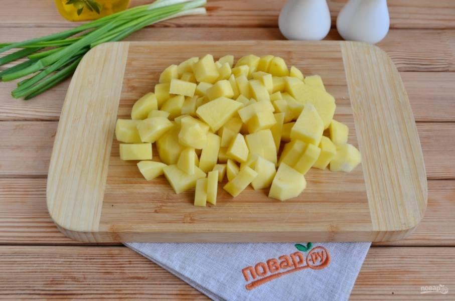 Очищенный картофель порежьте небольшими кубиками. Добавьте его в бульон и варите 15 минут.