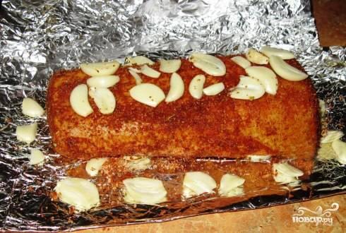 В миске смешиваем специи для свинины: соль, оливковое масло, и хорошо натираем остывшее мясо. Чеснок нарезаем пластинками и обкладываем со всех сторон карбонад.
