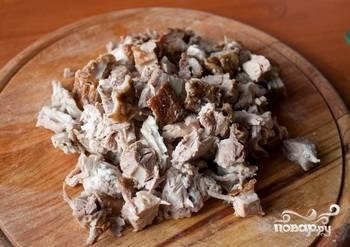 Сваренное мясо достаем из супа и оббираем мясо с косточек. Нарезаем его и отправляем обратно в кастрюлю.