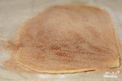 1. Предварительно разогреть духовку до 220 градусов. Выстелить два противня пергаментной бумагой или силиконовыми ковриками. Смешать в миске сахар, корицу и соль. Слегка посыпать сахарной смесью чистую рабочую поверхность или чистое кухонное полотенце. Раскатать слоеное тесто на рабочей поверхности в прямоугольник размером 30Х37 см. Равномерно распределить по тесту сахарную начинку.