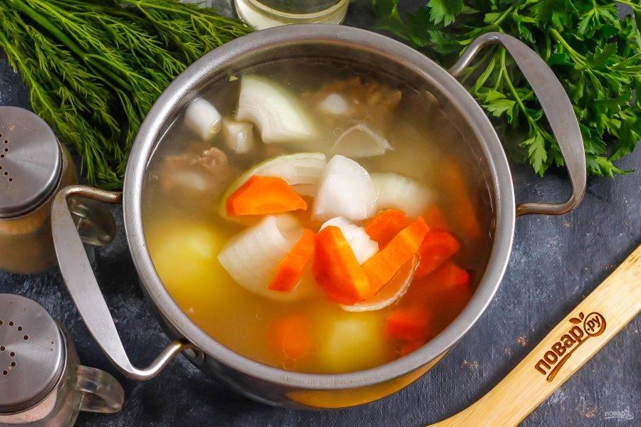 Нарежьте крупными кусочками лук и морковь, добавьте в емкость и отварите еще 5 минут. Всыпьте соль и молотый черный перец.