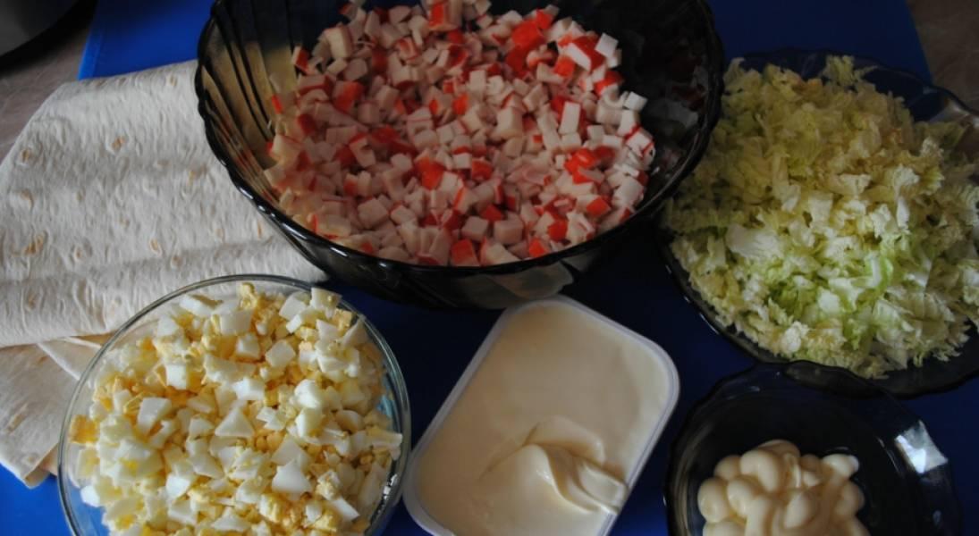 1. Подготовим ингредиенты. Яйца отварим, остудим и мелко нарежем. Также измельчим салат и крабовые палочки. Смешаем вместе салат, крабовые палочки, яйца и майонез. Специи - по вкусу.