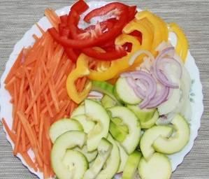 Подготовим овощи, тщательно их промойте. Морковь почистить и нарезать очень тонкой соломкой, кабачки режем кружочками, лук порезать полукольцами, болгарский перец  нарезаем соломкой.
