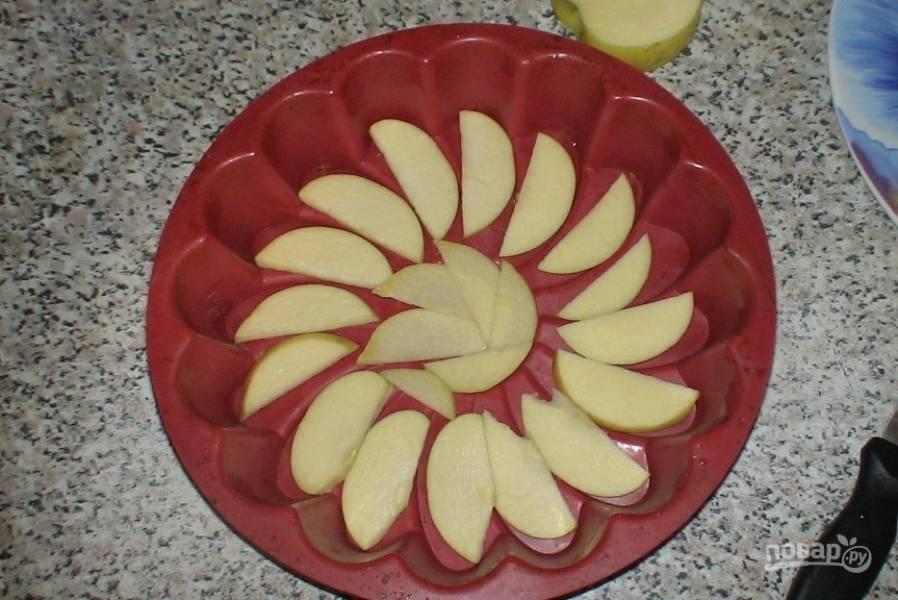 Яблоки очистите от кожуры и удалите серединку с семенами. Нарежьте их на дольки одинаковой величины. Возьмите силиконовую форму для запекания и выложите дольки яблок на ее дно максимально равномерно.