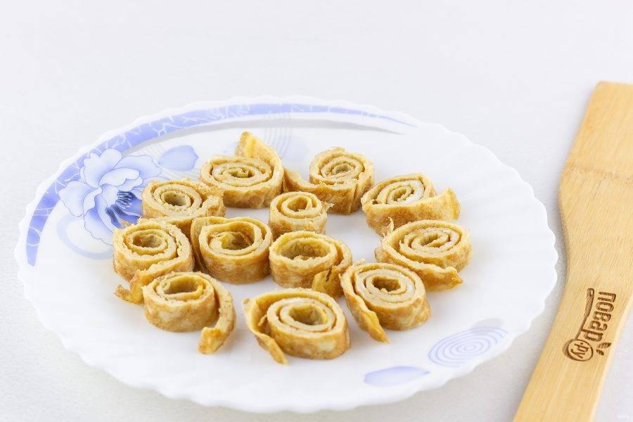 Остывший омлет сверните в рулет и нарежьте порциями по 0,5 см толщиной.