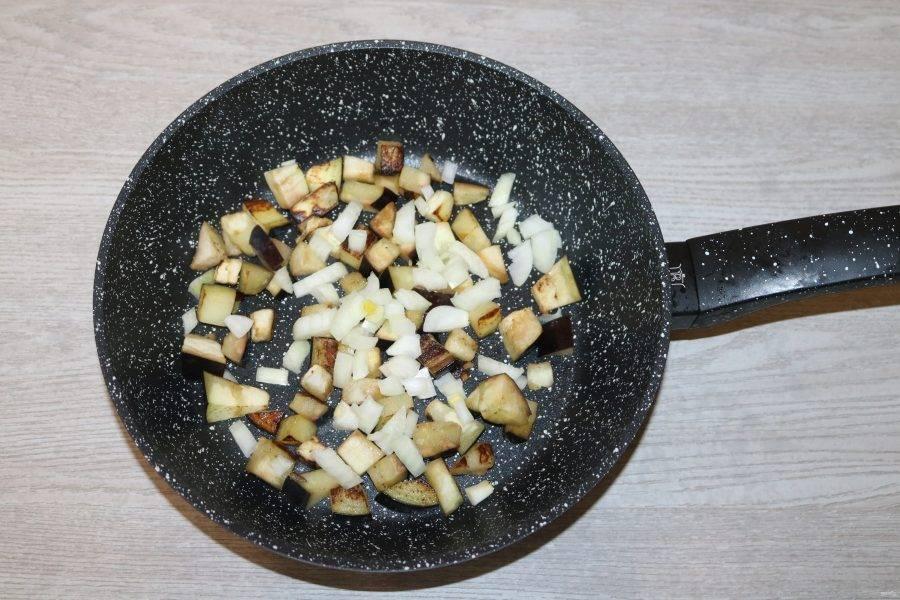 К баклажанам добавьте лук, обжаривайте вместе.
