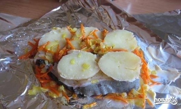 3.Кусочек фольги смазываю сливочным маслом, выкладываю на него сначала картошку, а затем поджарку. Мою рыбу, нарезаю её, вытираю насухо и кладу на овощи, солю и перчу, а затем снова кладу наверх картошку и поджарку.