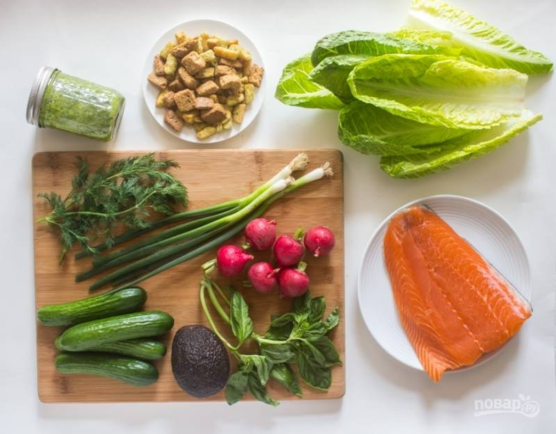 Подготовьте все необходимые ингредиенты для салата. Промойте и порежьте колечками редис и огурцы. Очистите и порежьте тонкими ломтиками авокадо. Зелень измельчите.