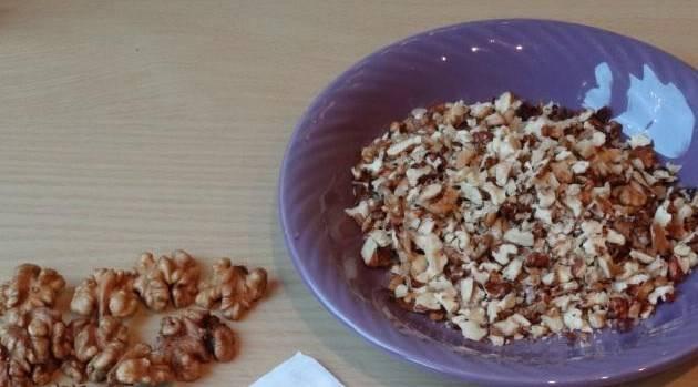 Орехи измельчите, оставьте крупные красивые орешки для украшения готовой халвы.