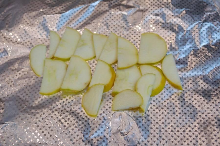 Лист фольги сложите втрое. Сладкое сочное яблоко нужно нарезать на тонкие дольки, выложите их на фольгу. На подушку из яблок мы уложим карбонат.