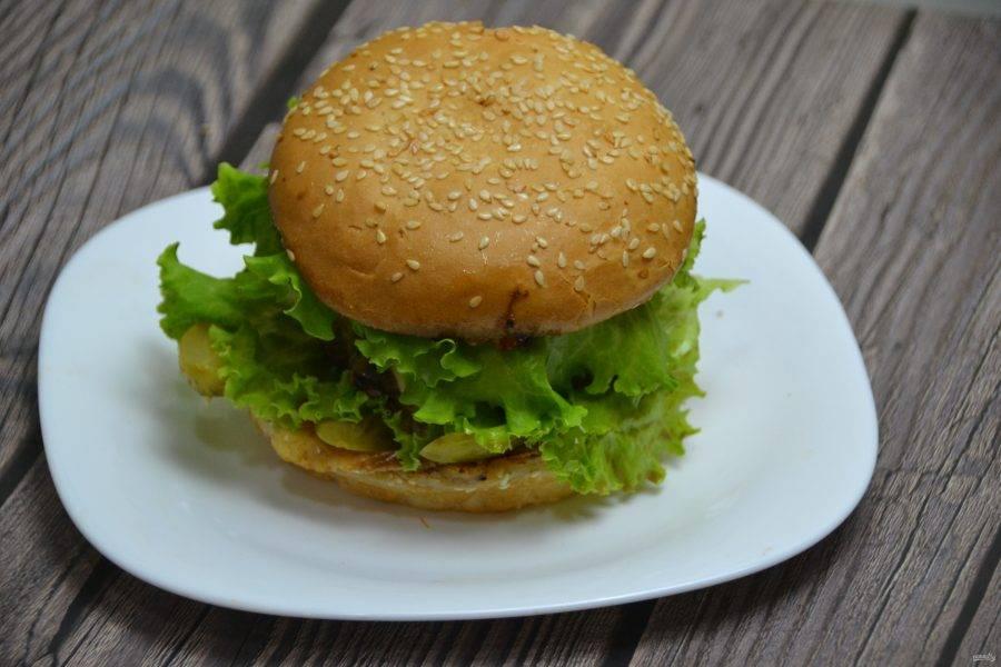 Накройте салатным листом и верхней частью булочки, которой предварительно соберите остатки расплавленного сыра со сковороды. Бургер готов к подаче, он вкусный и сытный, практически полноценный обед или ужин.