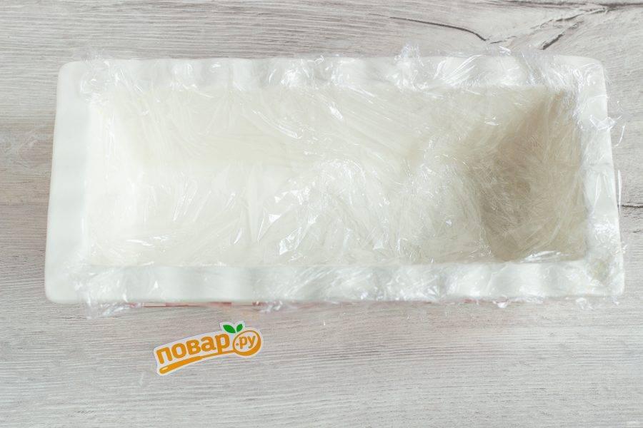 Прямоугольную форму застелите пищевой пленкой.