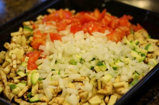 Для начала мы тщательно промываем овощи, затем нарезаем их на небольшие кубики. В глубокой посуде приправляем овощи любимыми специями, солим их и перемешиваем. Выкладываем овощи на смазанный растительным маслом противень.