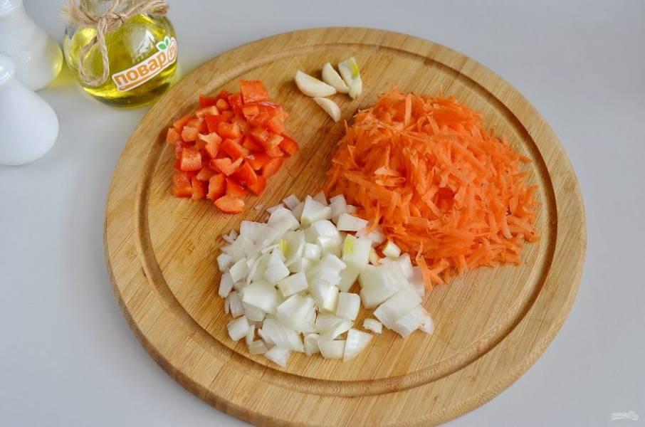 2. Очистите овощи, порежьте лук и болгарский перец кубиками, морковь натрите на крупной терке, чеснок на 4 части.