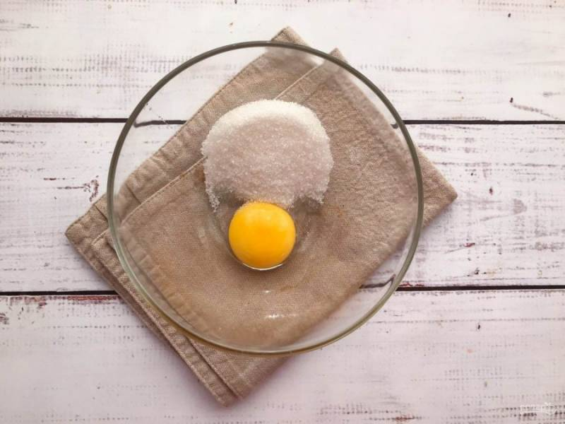 В глубокой тарелке соедините яичный желток с сахаром, солью и хорошо разотрите вилкой.