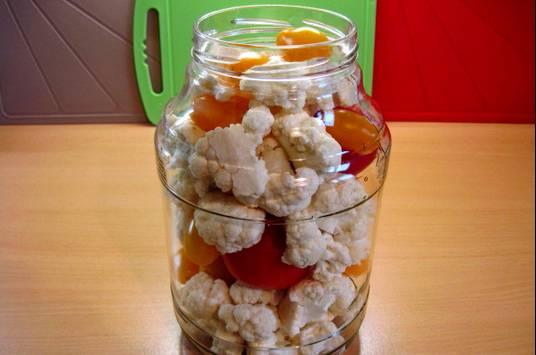 1. Капусту и помидоры моем, даем воде стечь. Капусту делим на соцветия, помидоры нарезаем средними кусочками. Укладываем плотно в банку, чередуя помидоры и капусту.
