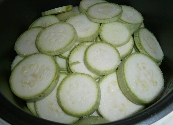 Кабачки промываем и срезаем с них кожуру, если они молоденькие, то можно и не чистить их. Нарезаем кабачки кольцами и выкладываем в чашу поверх остальных овощей, посыпаем их солью.