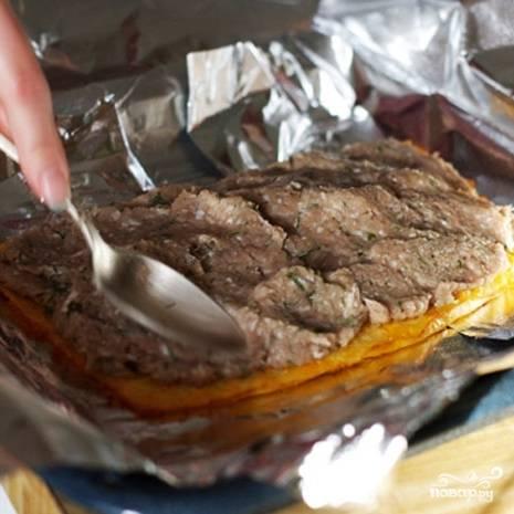 В центр фольги выкладываем лист сырного теста, промазываем его третьей частью начинки.