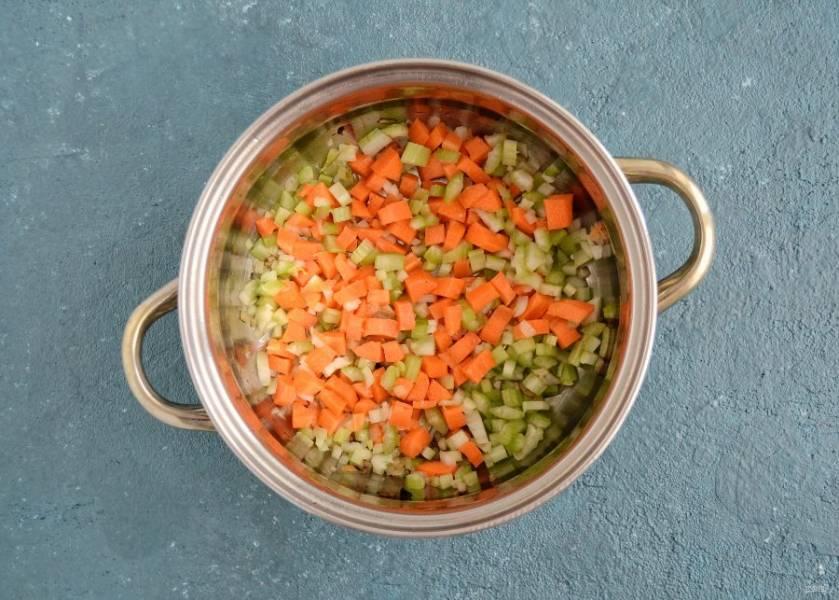 Нарежьте морковь, сельдерей и лук кубиками. Обжарьте их в кастрюле с 2 столовыми ложками масла.