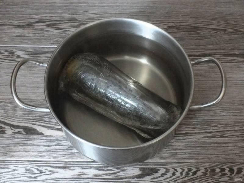 В широкую кастрюлю налейте воду, доведите до кипения. Опустите в неё подготовленную рыбу и варите при слабом кипении 35 минут.