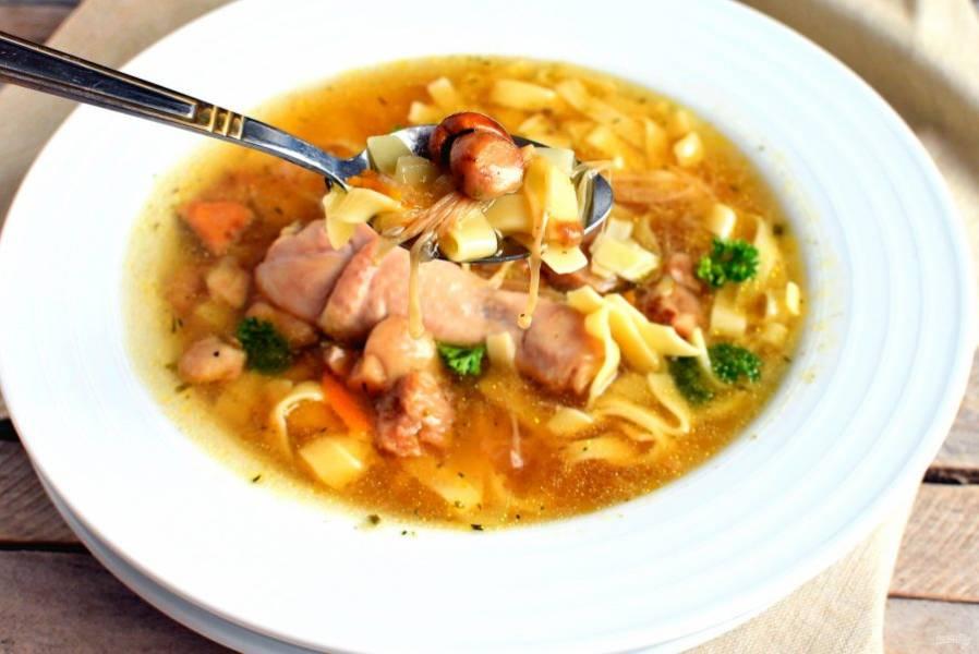 Отварите отдельно домашнюю лапшу, откиньте на дуршлаг, дайте хорошо стечь и разложите по глубоким тарелкам. Залейте супом и подавайте на стол сразу же, украсив суп зеленью.