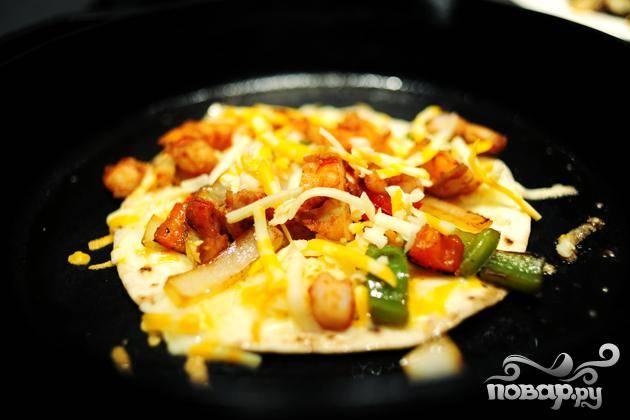 4. В отдельной сковороде нагреть масло. Выложить в сковородке, затем слой тертого сыра, овощи и креветки. Посыпать еще небольшим количеством сыра сверху и накрыть второй лепешкой. Жарить на обеих сторонах, добавляя масло перед переворачиванием, так как лепешки не должны быть сухими.