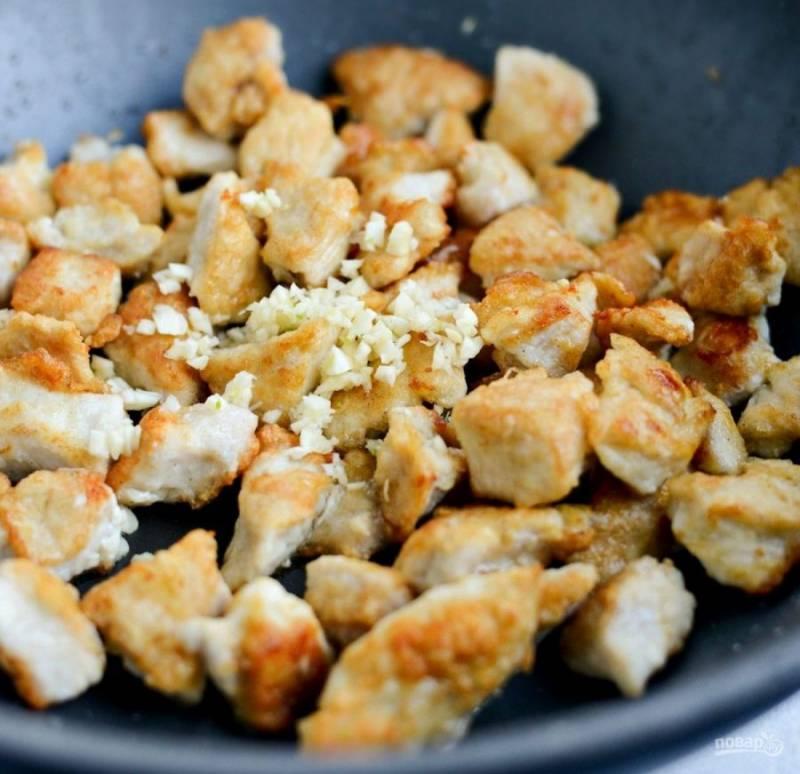 Потом верните всю курице на сковороду и добавьте измельчённый чеснок. Подержите ингредиенты на огне 2 минуты.