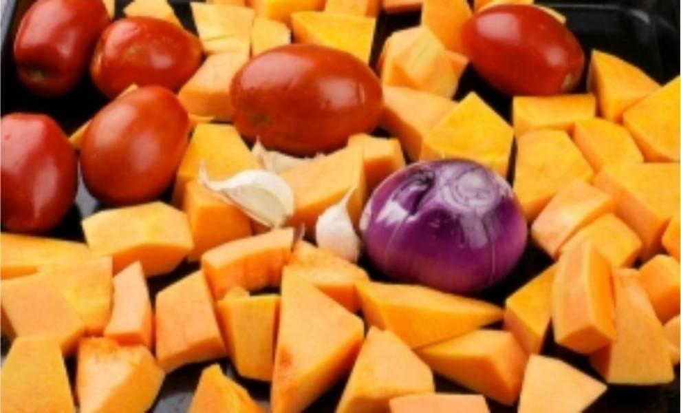 2. Теперь пришло время заняться супом. Тщательно моем все овощи. Тыкву очищаем от семян и кожуры и режем на средние куски, лук чистим и надрезаем, чеснок очищать не надо. После все овощи вместе с помидорами выкладываем на противень.