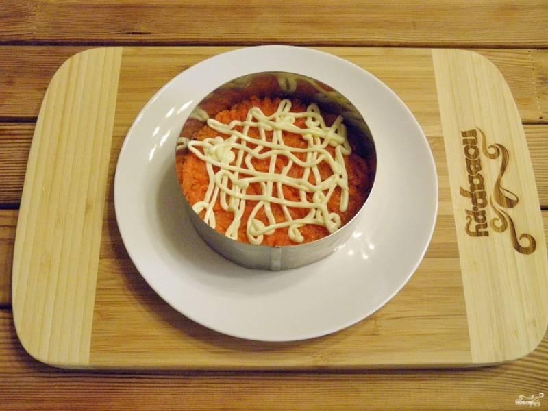 Второй слой - морковь, специи и майонез. Вилочкой утрамбовывайте немного салат.