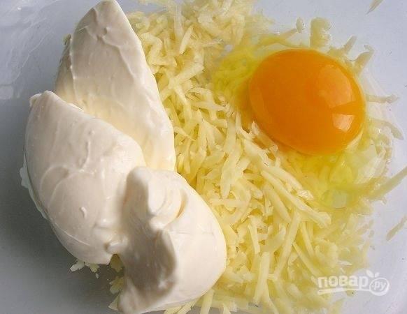4. Половину тертого сыра выложите в глубокую мисочку. Вбейте 1 яйцо, добавьте майонез. Посолите по вкусу и тщательно перемешайте.