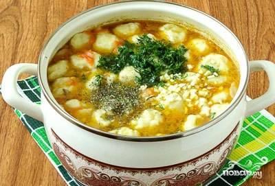 Как только клёцки всплывут, добавьте в суп измельчённый чеснок с зеленью. Проварите ещё 4 минуты.