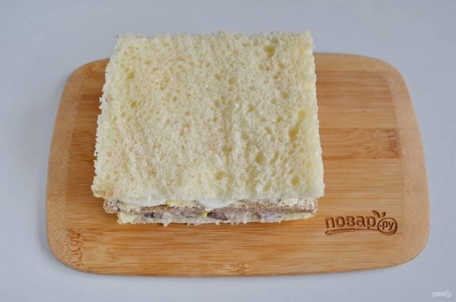 Накройте вторым кусочком белого хлеба. Придавите немного ладошкой торт.