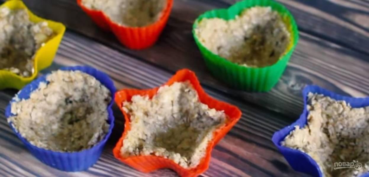1. С помощью толкушки превратите банан в пюре, добавьте овсяные хлопья и мед. Перемешайте, чтобы получилось тесто. Формы для кексов смажьте сливочным маслом и распределите по их бортикам тесто так, чтобы получились чашечки.