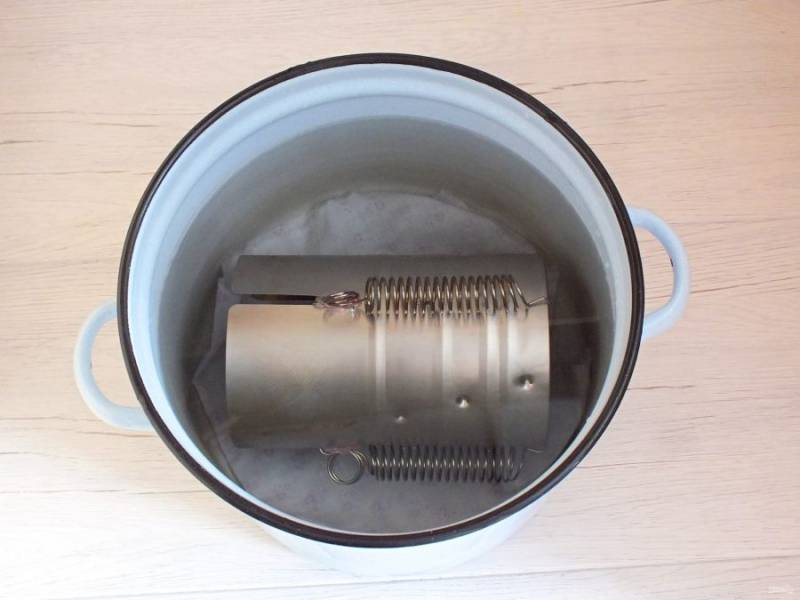 Возьмите большую кастрюлю. На дно выложите ткань. Положите на бок ветчинницу и залейте водой так, чтобы ветчинница полностью была покрыта жидкостью. Поставьте на средний огонь, доведите до кипения и убавьте огонь до малого. Варите 1 час 30 минут. По истечении времени выключите огонь, слейте воду.