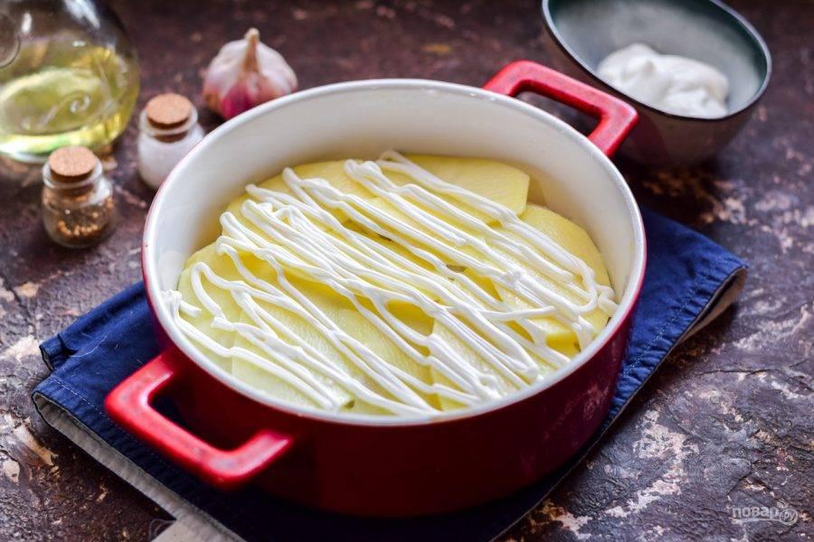 Смажьте картофель сметаной.