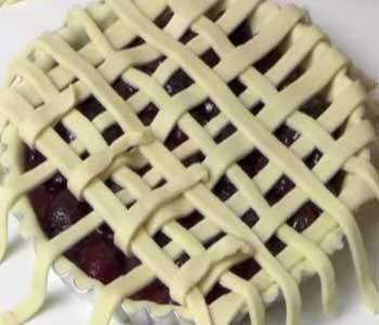 Остаток теста порежьте на тонкие лоскуты-полосочки и выложите их сеткой на пироге.  Поле отправьте пирог в разогретую духовку, выпекайте его при температуре в 200 градусов до готовности. На это у вас уйдет около 30-40 минут. Перед подачей на стол обязательно остудите его.