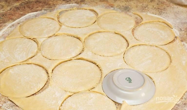 10. Поднявшееся тесто выкладываю на стол, затем раскатываю его в пласт толщиной до 1 сантиметра, затем с помощью блюдца вырезаю ровные круги.