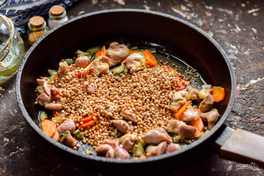 Всыпьте в сковороду гречневую крупу, добавьте немного соли и перца.