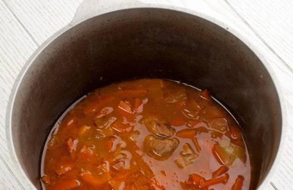 В казанок кладем мелко нарезанный лук и морковь брусочками. Обжариваем до золотистого цвета овощи, затем добавляем томатный соус и обжаренное мясо. Тушим 5 минут.