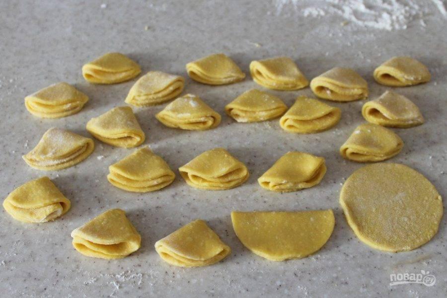 Каждый кружок теста согните пополам, а потом еще раз пополам. Получаются сложенные четвертушки. Выпекайте творожное печенье на противне с пергаментом при температуре 180 градусов (12-15 минут).