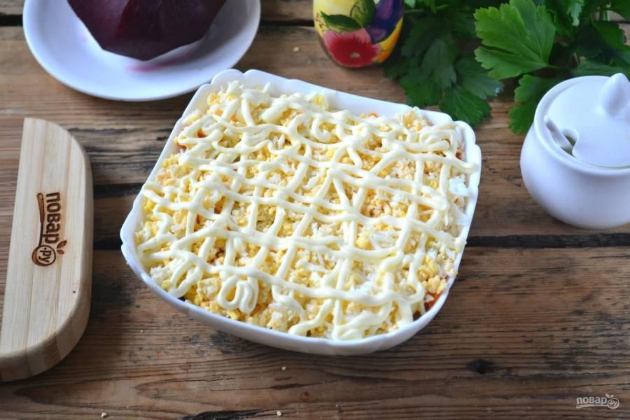 Натрите на мелкой терке яйца, сваренные вкрутую, и выложите их на морковь, сверху сделайте майонезную сеточку.