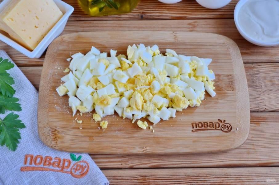 Порежьте вареные яйца. Если они мелкие, то отварите три штуки. Соедините яйца с зеленью, добавьте щепотку соли, перца, перемешайте начинку.