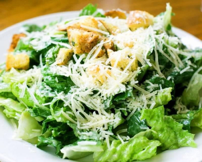 Листья салата заправить соусом и перемешать. Выложить сухарики и полить оставшимся соусом. посыпать тертым пармезаном. Подавать на стол сразу.