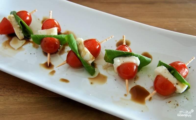 Нанизываем на шпажки или зубочистки поочередно помидоры, моцареллу и базилик. Выкладываем на красивое блюдо, сверху сбрызгиваем оливковым маслом и бальзамическим уксусом - готово!
