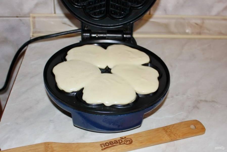 Хорошо нагрейте вафельницу, немного смажьте маслом и выложите тесто.